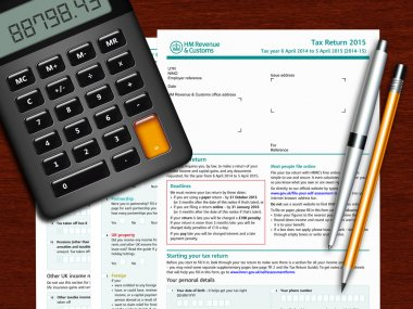 SA100 tax return form with calculator and pencil on wooden table