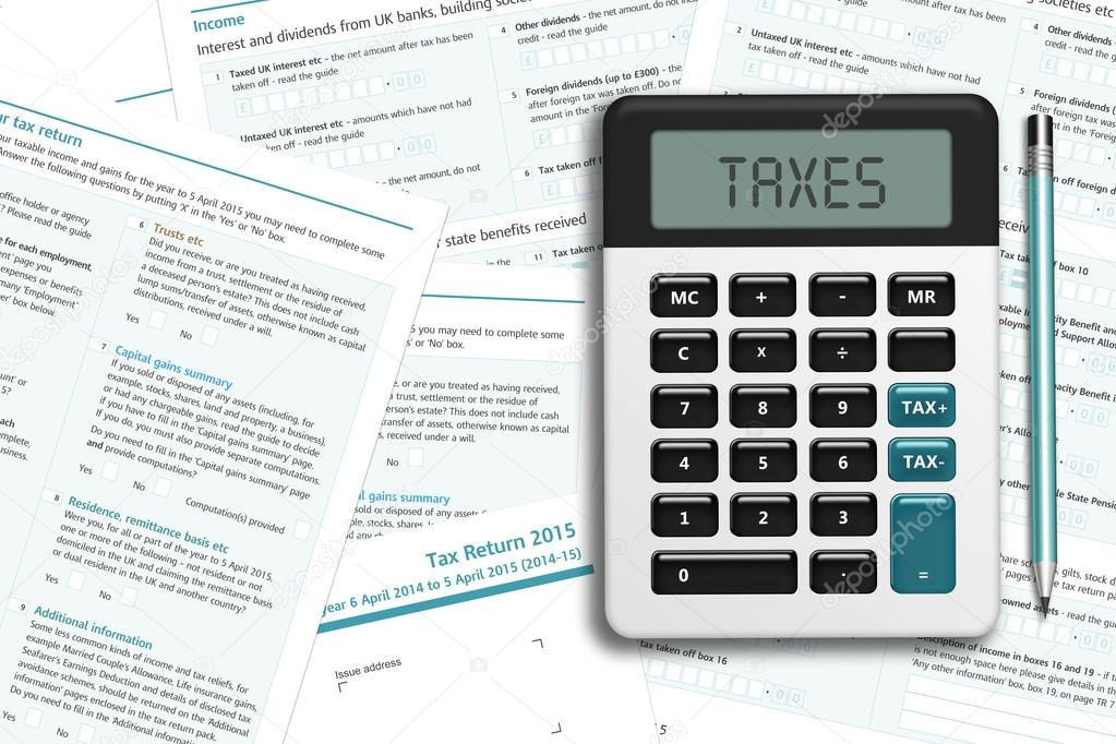 UK tax form with calculator lying on wooden desk — Stock Photo