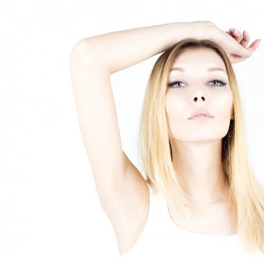 Beautiful woman on a white background with her hand raised. Waxing armpit. Epilation result. Smooth and fresh skin