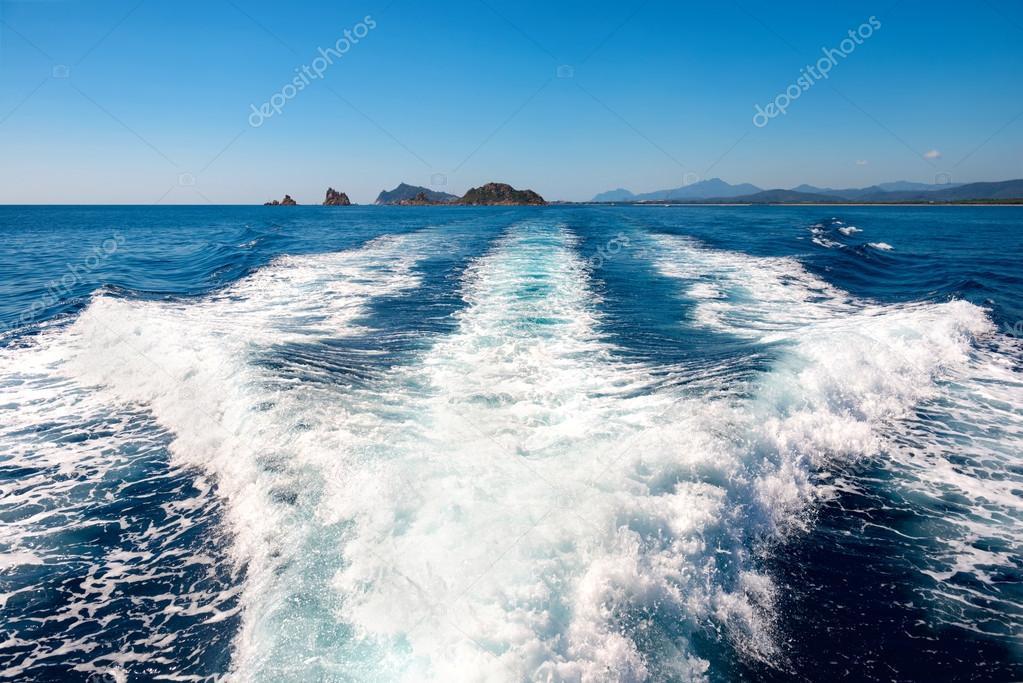 Waves on blue sea behind boat