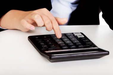 Business womans hands counts on the calculator