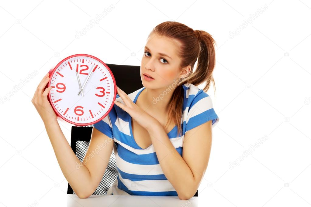 teenage woman looking at clock stock photo piotr marcinski