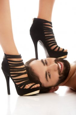 Womans foot on mans face.