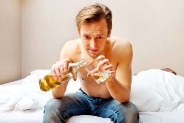 Drunk man sitting on bed and drinking whiskey
