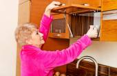 Starší žena úsměv hrnek z kuchyňské linky