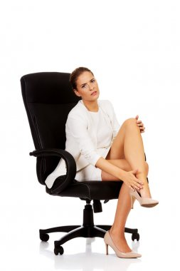 Businesswoman with leg pain sitting on the armchair. stock vector