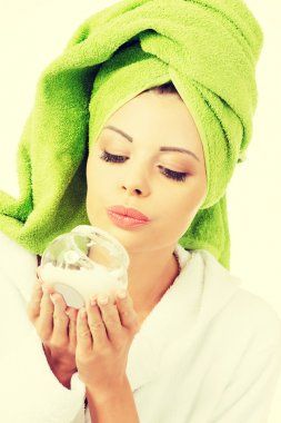 Beautiful woman in bathrobe, turban and holding face cream.