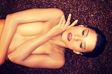 Beautiful topless woman lying on coffee beans.