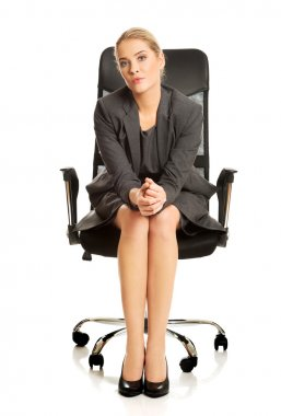 Confident businesswoman sitting on armchair, looking at the camera. stock vector