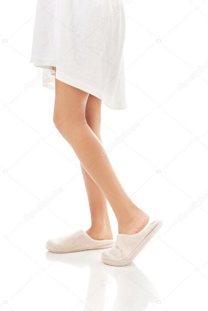 Side view of female feet in white slippers