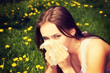 Attractive young woman outdoor with tissue.