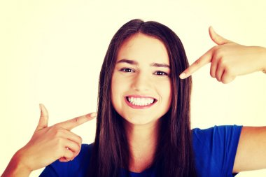 Woman pointing on her perfect white teeth.
