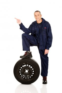 Repairman with leg on a tire