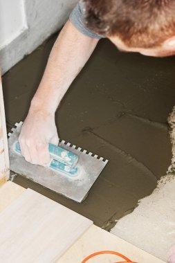 Tiler installs ceramic tiles