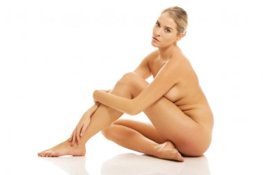 Naked woman sitting on floor