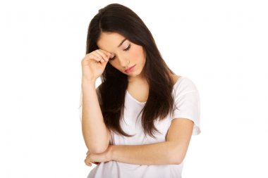 Depressed teen woman touching head.