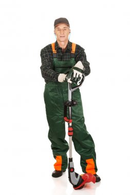 Gardener with trimmer and ear protectors
