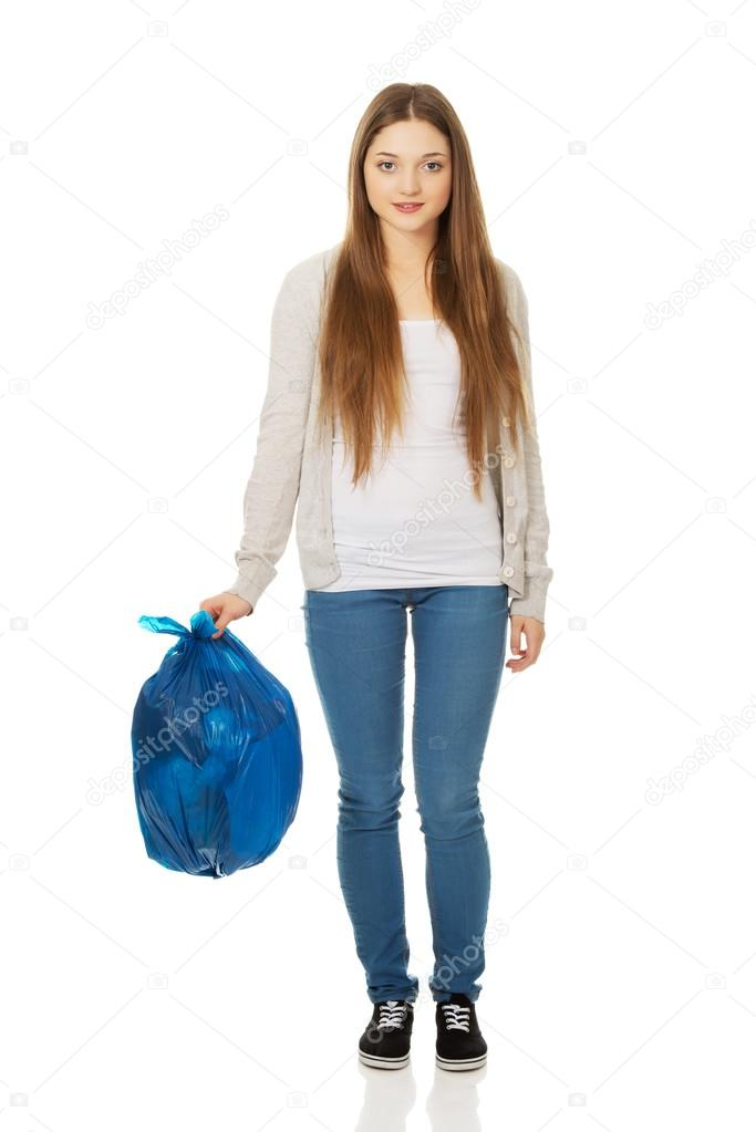 Happy woman holding a full garbage bag.