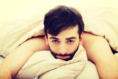 Man waking up in bedroom.