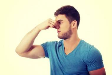 Young man pinching his nose.