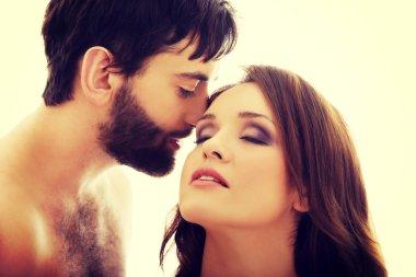 Shirtless man whispering to womans ear.