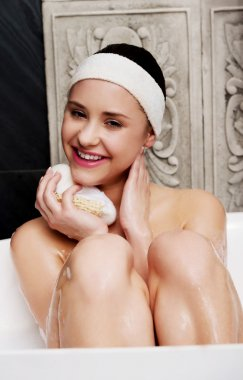 Bathing woman relaxing with sponge.