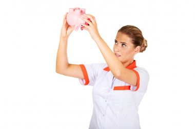 Young female doctor or nurse holding a piggybank