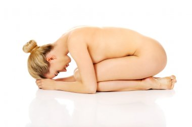 Young naked woman sitting curled up