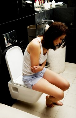 Caucasian woman is sitting on the toilet.
