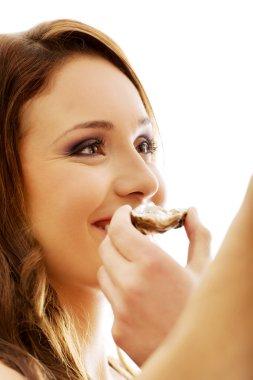 Man feeding woman with fresh oyster.