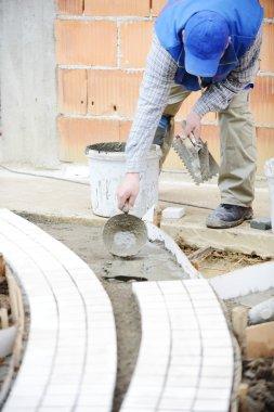Mason worker making sidewalk pavement