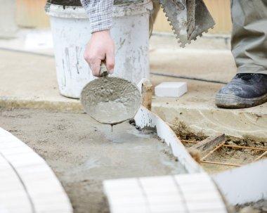 Worker making sidewalk pavement