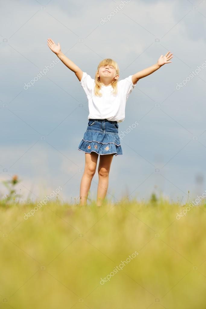 Llittle blonde girl on summer grass meadow