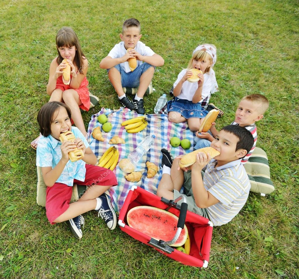 Children having picnic on meadow — Stock Photo © zurijeta #98579300