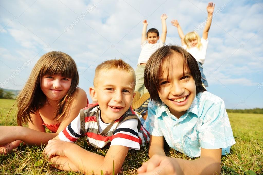 Group of happy children on summer grass meadow