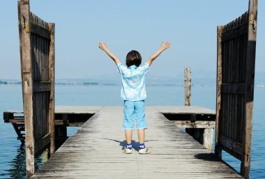 Kid running and jumping on sea dock
