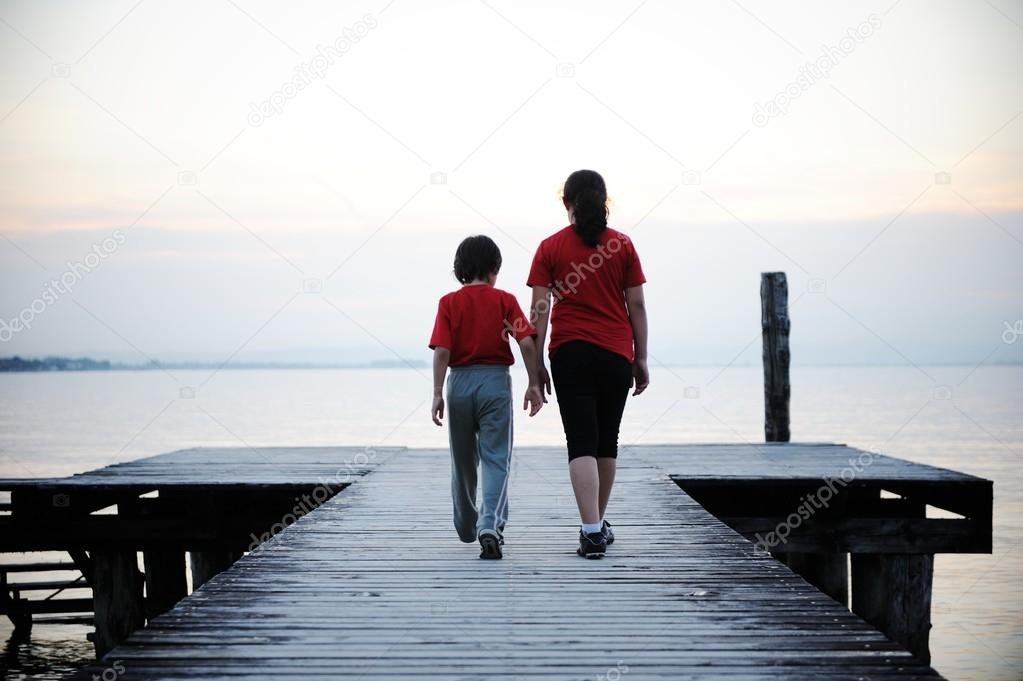 Sister and brother on wooden dock