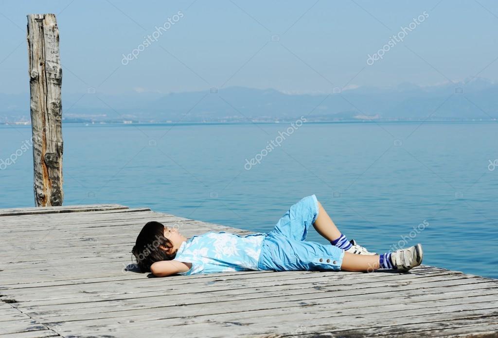 Boy on a beautiful lake dock