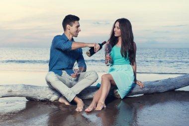 Couple drinking wine on the beach