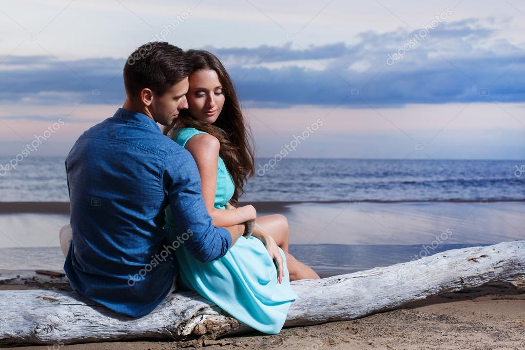Lovely couple sitting on the beach