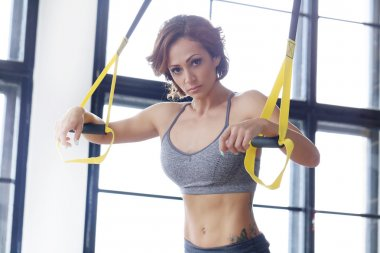 Beautiful woman training with TRX