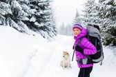 Šťastná žena chůze v zimním lese se psem