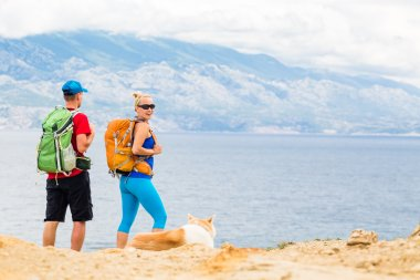 Couple hikers walking with dog at seaside and mountains