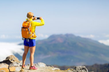 Woman hiker taking photos  in mountains
