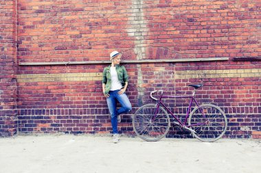 Young woman with vintage road bike in city