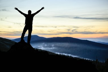 Man hiker successful with arms outstretched