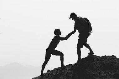Teamwork couple hiking climbing helping hand