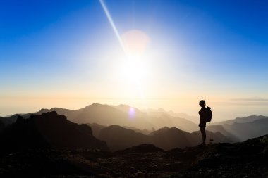 Woman hiking success silhouette in mountains sunset