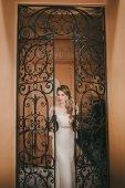 Fotografia Sposa che propone vicino alla porta in ferro battuto