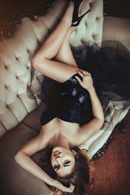 Sexy beautiful blonde girl in black dress lying on sofa stock vector